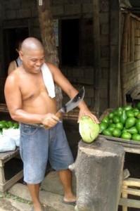 Uomo filippino utilizza un bolo per tagliare una noce di cocco